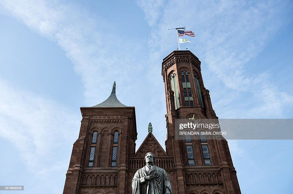 A statue of Joseph Henry, the first Secretary of the Smithsonian Institution, is seen in front of the Smithsonian Castle, the headquarters for the Smithsonian Institution, May 3, 2013 in Washington, DC. AFP PHOTO/Brendan SMIALOWSKI