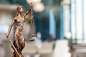 A bronze statue of the Lady Of Justice  composited into a blur background of a law firm.