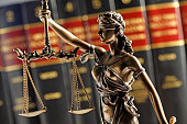Statue of lady justice stands in front of an out of focus row of law books.