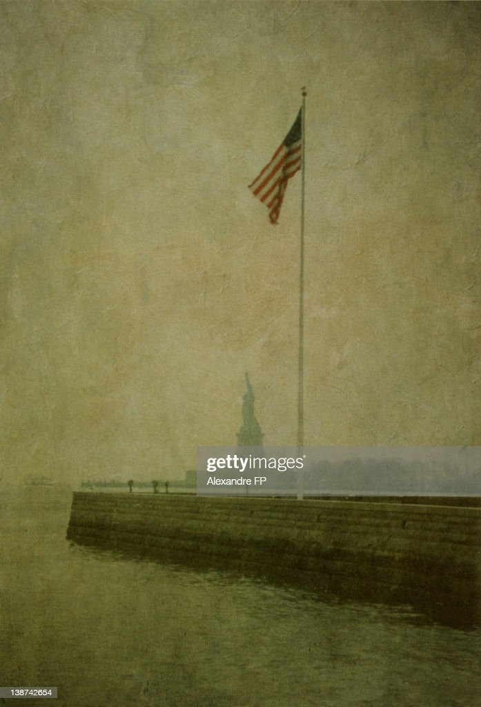 Statue of Liberty and American Flag on flagpole : Stock Photo
