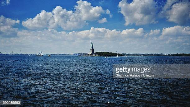 Statue Of Liberty At Seaside Against Cloudy Sky