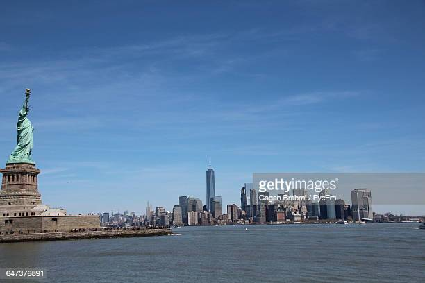 Statue Of Liberty By River Against Sky In City