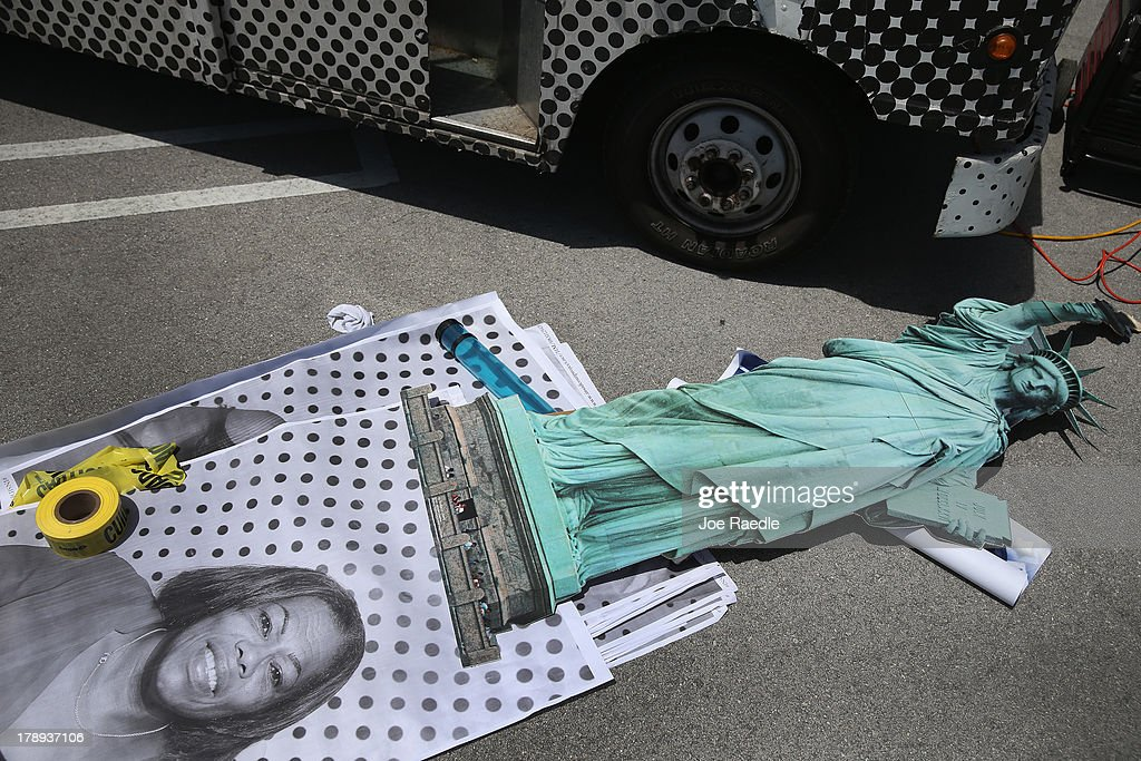 A Statue of Liberty cutout is seen near a photograph laying on the ground during the installment of the 'Inside Out 11M' project on the walls of the Freedom Tower on August 31, 2013 in Miami, Florida. The public art project puts a face on immigration reform by creating a massive mosaic of portraits taken on site, printed immediately and pasted on the Freedom Tower at Miami-Dade College.