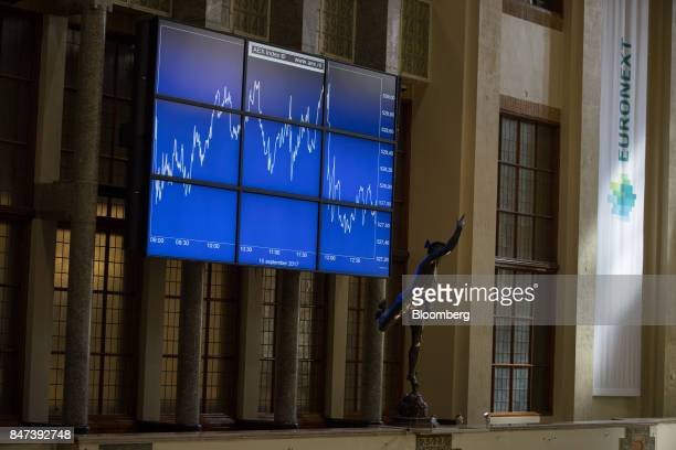 A statue of Mercurius stands in front of a screen displaying the AEX Index curve inside the Amsterdam Stock Exchange operated by Euronext NV in...