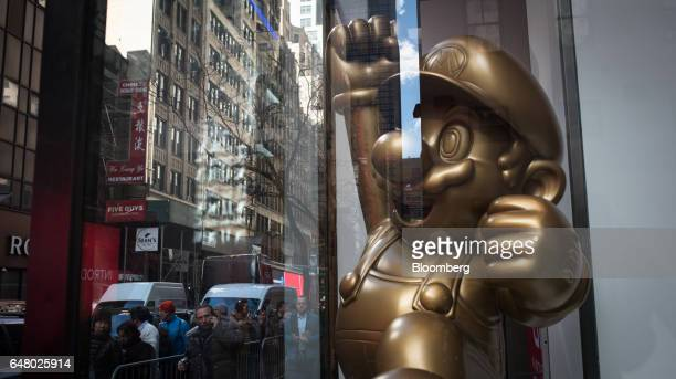 A statue of Nintendo Co's videogame character Mario is displayed as customers wait in line outside of the company's store to purchase the Nintendo...