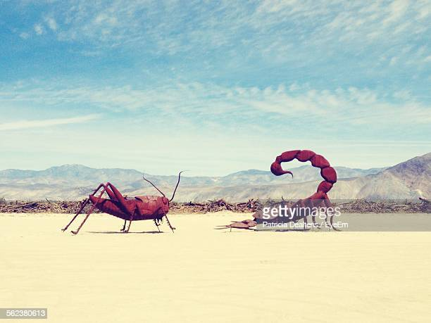 Statue Of Scorpion And Grasshopper Against Sky