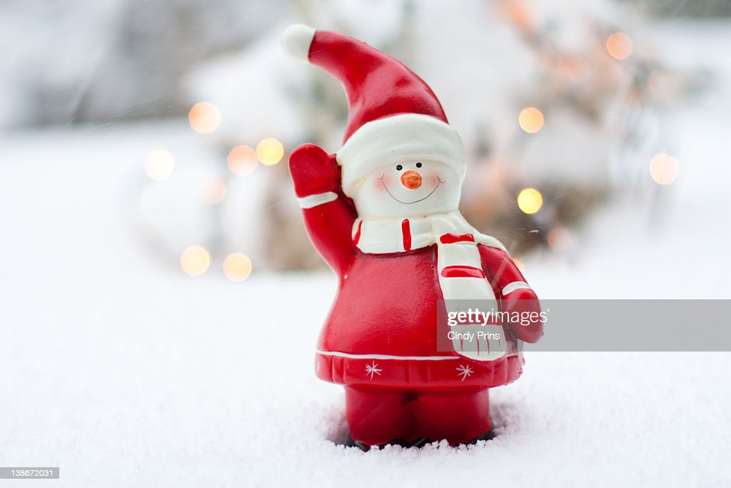 Statue of snowman waving in snow : Stock Photo
