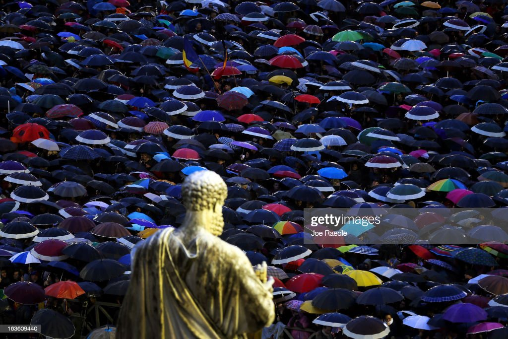 A statue of St Peter looks down upon people sheltering from the rain under umbrellas as they gather in St Peter's Square as they wait for news on the election of a new Pope on March 13, 2013 in Vatican City, Vatican. Pope Benedict XVI's successor is being chosen by the College of Cardinals in Conclave in the Sistine Chapel. The 115 cardinal-electors, meeting in strict secrecy, will need to reach a two-thirds-plus-one vote majority to elect the 266th Pontiff.