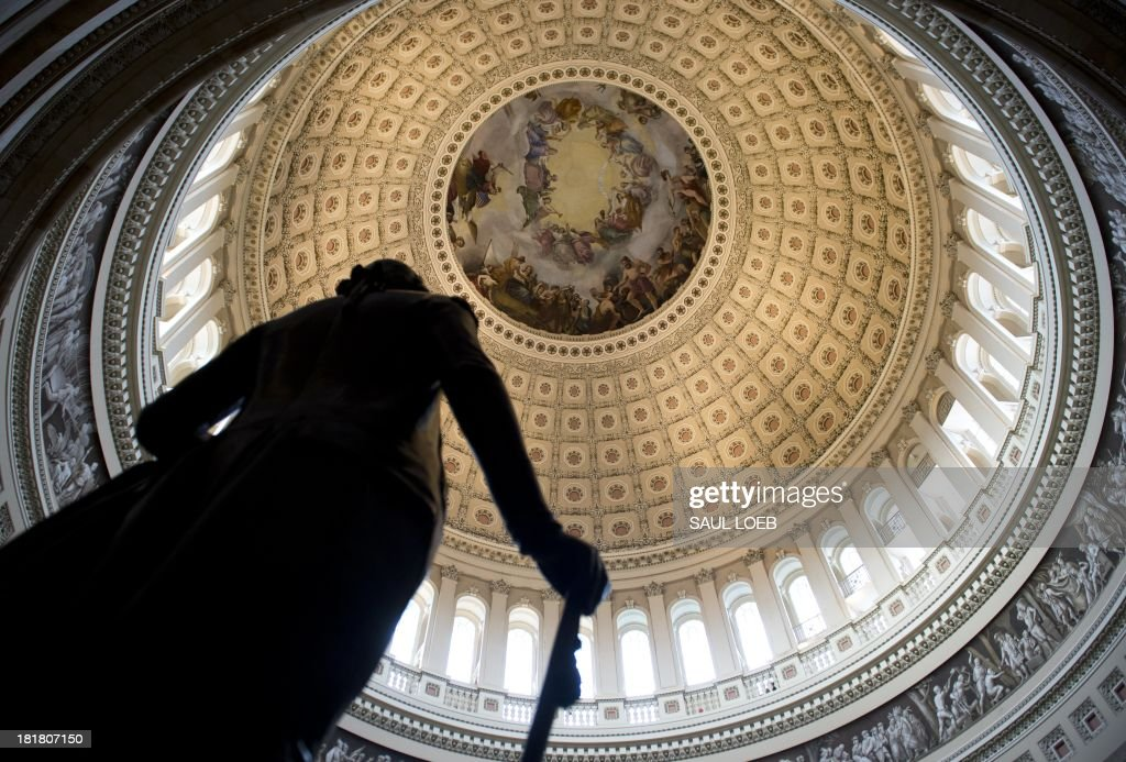 A statue of the first US President, George Washington, is seen in the Rotunda of the US Capitol in Washington, DC, September 25, 2013. With the clock ticking toward a possible US government shutdown, the US Senate voted unanimously Wednesday to advance a stopgap spending bill that would avoid federal closures. The 100-0 vote masks deep divisions within Congress over what course to take in the next five days to thrash out a temporary measure that funds government operations beyond September 30, the final day of the current fiscal year. AFP PHOTO / Saul LOEB