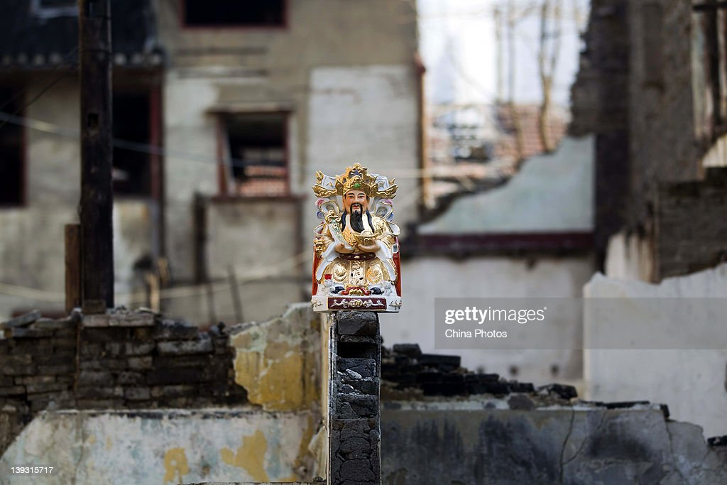 A statue of the God of Fortune is seen in front of houses being demolished at the North Bund on February 19, 2012 in Shanghai, China. According to local media, the North Bund area will be reconstructed as a international shipping and financial zone, a modern commercial and high-end residential area, and recreation center.