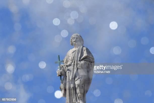 A statue of the Vatican is photographed through the water of a fountain during Pope francis' Angelus prayer at St Peter's square on March 26 2017 in...