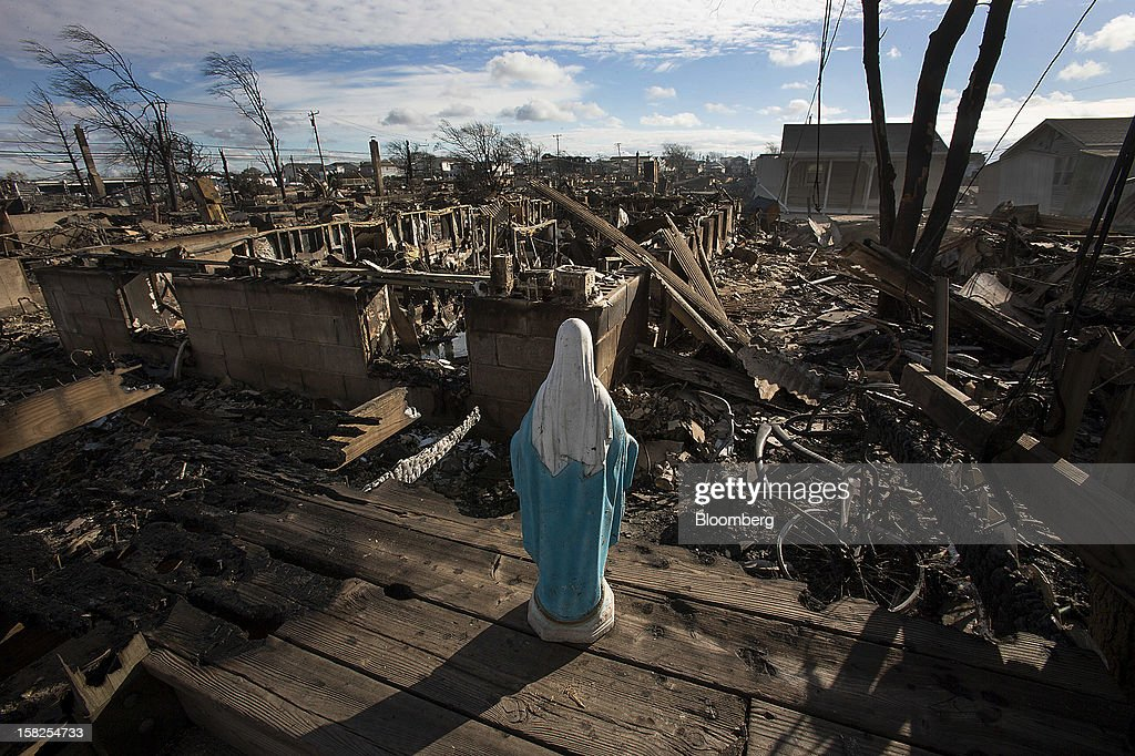 A statue of the Virgin Mary stands over houses destroyed by fire in the Breezy Point neighborhood of the Queens borough of New York, U.S., on Wednesday, Oct. 31, 2012. Atlantic superstorm Sandy may cut U.S. economic growth as it keeps millions of employees away from work and shuts businesses from restaurants to refineries in one of the nationís most populated and productive regions. Photographer: Scott Eells/Bloomberg via Getty Images