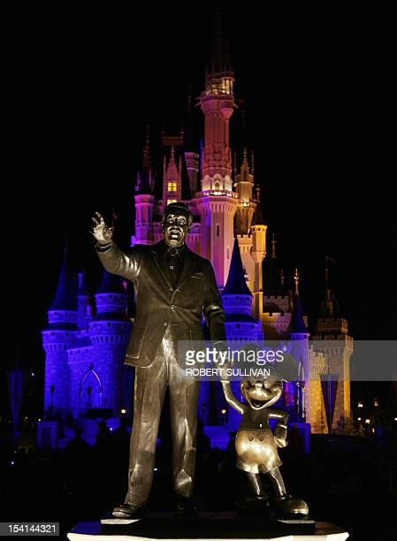 A statue of Walt Disney and Mickey Mouse in front of Cinderella's Castle at Walt Disney World 25 January 2007 in Lake Buena Vista Florida Disney is...