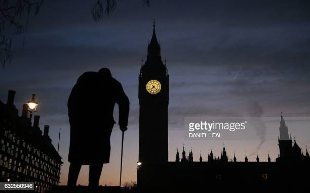 A statue of Winston Churchill is silhouetted by the Elizabeth Tower more commonly known as 'Big Ben' and the Houses of Parliament in central London...