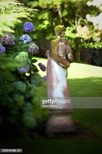 Statue of woman in garden, rear view (focus on head)