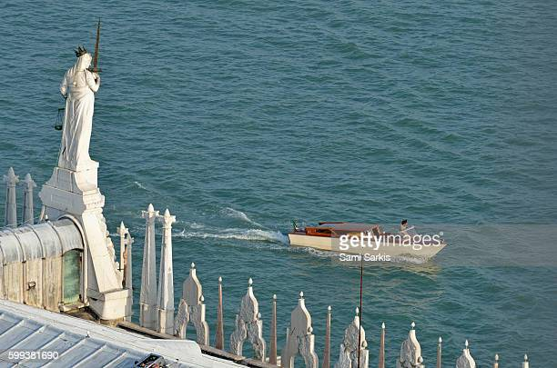 Statue on the Doges Palace facing the Venetian lagoon, Venice, Italy, Europe as a small motorboat passes