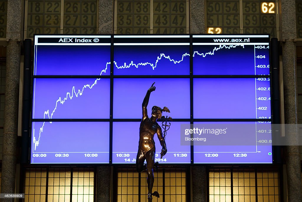 A statue stands in front of the AEX index curve as it is displayed on an electronic board inside the Amsterdam Stock Exchange, operated by Euronext NV, a unit of IntercontinentalExchange Group Inc. (ICE), in Amsterdam, Netherlands, on Tuesday, Jan. 14, 2014. ICE plans to sell as much as 30 percent of Euronext NV before the operator of the Paris and Amsterdam exchanges goes public this year, three people with knowledge of the matter said. Photographer: Jasper Juinen/Bloomberg via Getty Images