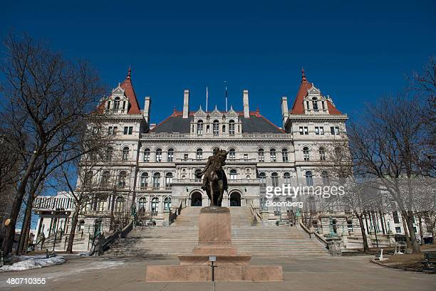 A statue stands in front of the New York State Capitol building in Albany New York US on Wednesday March 19 2014 Budget talks among New York Governor...