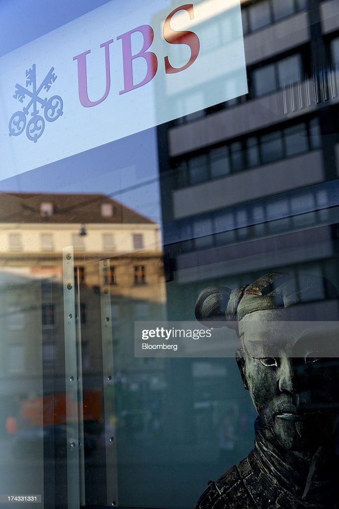 A statue stands in the window of a UBS AG bank branch as it shows reflections of buildings in Basel, Switzerland, on Tuesday, July 23, 2013. Europe's biggest banks, which more than doubled their highest-quality capital to $1 trillion since 2007 to meet tougher rules, may have further to go as regulators scrutinize how lenders judge the riskiness of their assets. Photographer: Gianluca Colla/Bloomberg via Getty Images