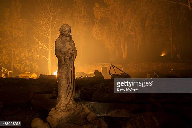 A statue stands next to the ruins of a house that burned down in the Butte Fire on September 12 2015 north of Murphys California The 100squaremile...