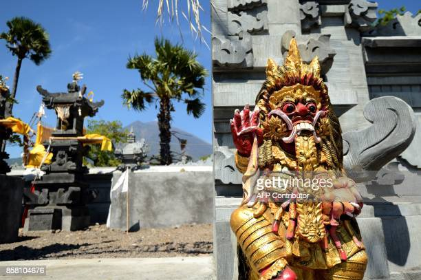 Statues at a Balinese temple are pictured as Mount Agung volcano looms in the background in the Kubu subdistrict in Karangasem Regency on Indonesia's...