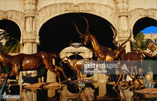 Statues of animals, deer and leopards, running over water at the entrance to the Palace of the Lost City Hotel