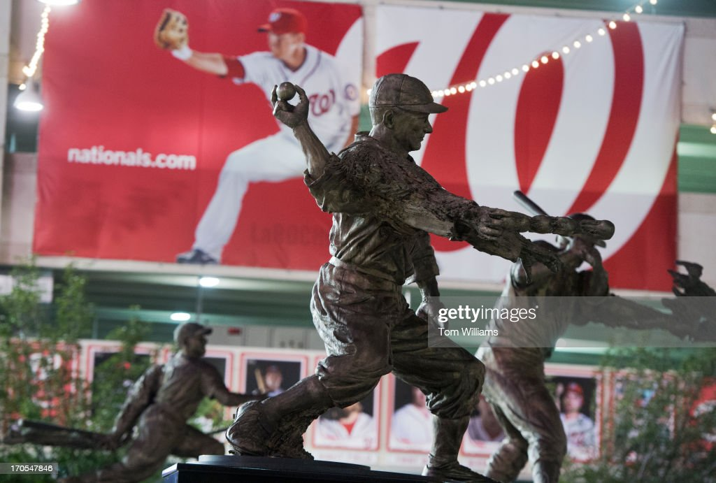 Statues of former Washington baseball players Walter Johnson, center, Frank Howard, right, and Josh Gibson, appear near the centerfield gate at Nationals Park. Current National Adam LaRoche appears on a banner in the background.