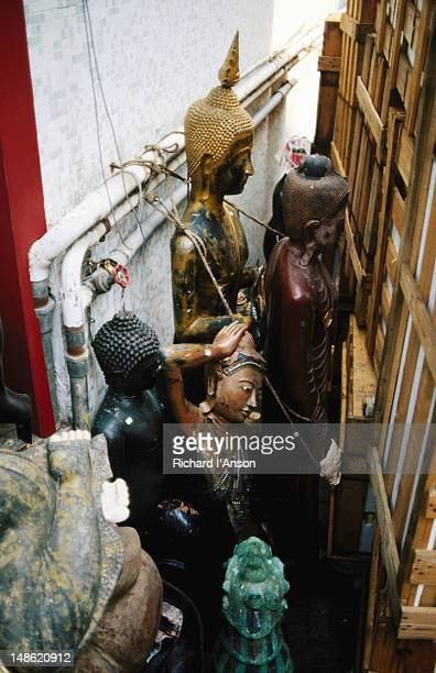 Statues of the Buddha wedged between a brick wall and some wooden packing crates behind a shop in Sheung Wan