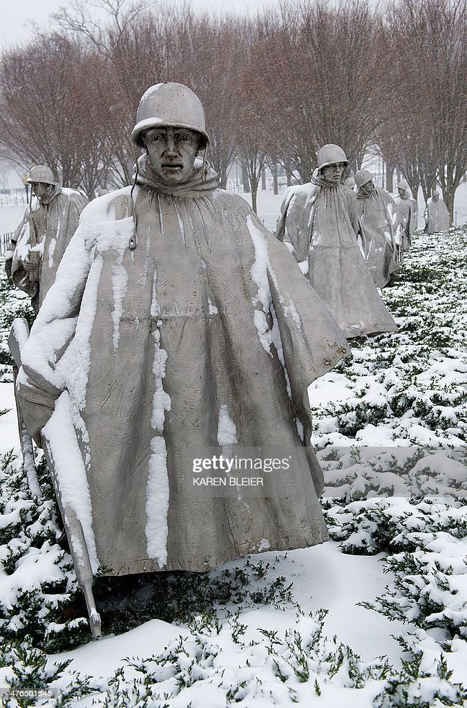 Statues of US troops at the Korean War Memorial are seen during a snow storm March 3, 2014 in Washington, DC. Snow began falling in the nation's capital early Monday, and officials warned people to stay off treacherous, icy roads a scene that has become familiar to residents in the Midwest, East and even Deep South this year. Schools were canceled, bus service was halted in places and federal government workers in the DC area were told to stay home Monday. AFP PHOTO / Karen BLEIER