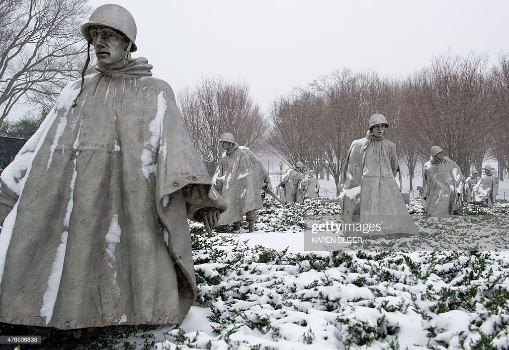 Statues of US troops at the Korean War Memorial are seen during a snow storm March 3 2014 in Washington DC Snow began falling in the nation's capital...