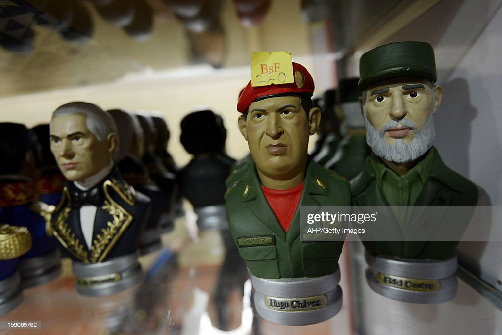 Statuettes depicting Venezuelan President Hugo Chavez (C), Cuban leader Fidel Castro (R) and Venezuelan Independence hero, Francisco de Miranda, are seen on display at a shop in Caracas on January 7, 2012. The church weighed in with four days to go before President Hugo Chavez, who is in Cuba recovering from cancer surgery, is supposed to be sworn in to a new six year term. Venezuela's Catholic church warned the government Monday it would be 'morally unacceptable' to override the constitution amid an intensifying crisis over Chavez's health. His vice president has argued that the swearing in can be delayed indefinitely, calling it a 'formality,' and that Chavez's current administration can continue in office until a new one can be sworn in. AFP PHOTO/Leo RAMIREZ