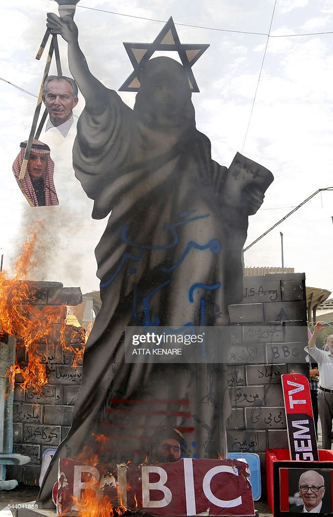 A statute depicting US' Statue of Liberty decorated with a Star of David on its head and holding portraits of former British prime minister Tony Blair and Saudi Foreign Minister Adel al-Jubeir is set ablaze by Iranian protesters during a parade marking al-Quds (Jerusalem) Day in Tehran on July 01, 2016. Tens of thousands joined pro-Palestinian rallies in Tehran, as the annual Quds Day protests take on broader meaning for a region mired in bitter disputes and war. On the bottom R a portrait of Australian born media magnate Rupert Murdoch. KENARE