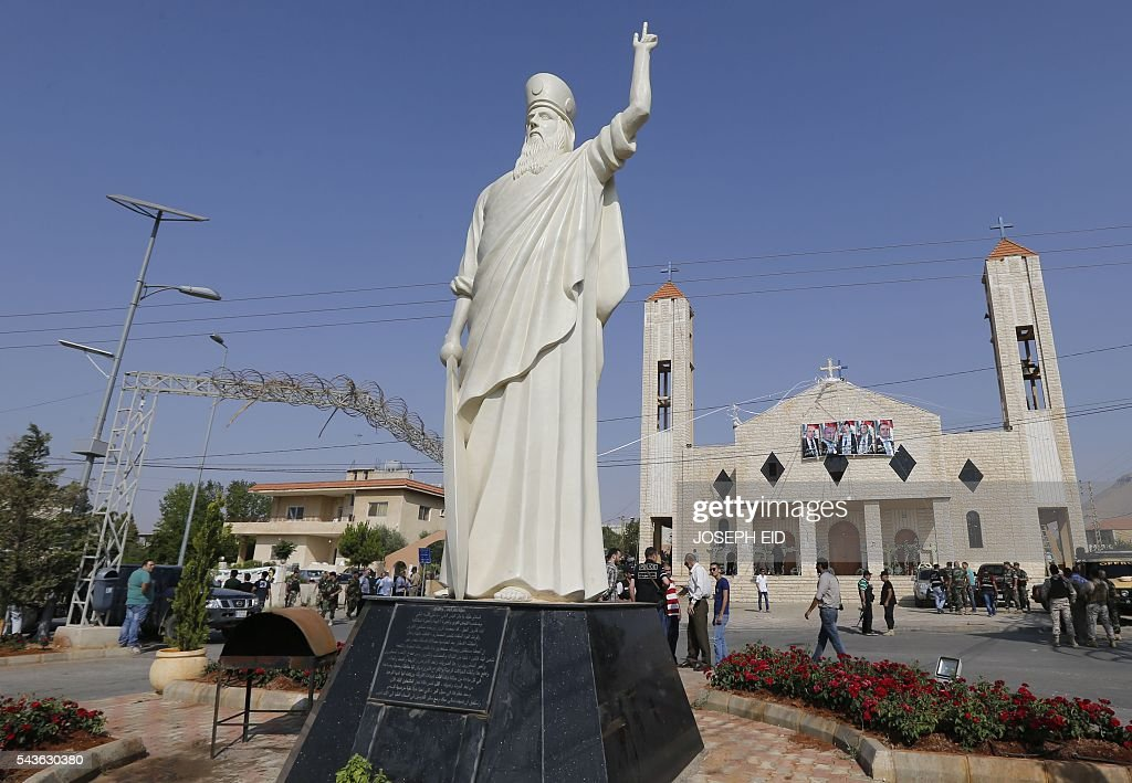 A statute of Saint Elie stands in front of a church where suicide attacks took place earlier this week in the village of al-Qaa, near the country's border with war-ravaged Syria, on June 29, 2016. Two waves of suicide bombings struck the predominantly Christian village on June 27, killing and wounding several people before dawn and in the evening. / AFP / JOSEPH EID