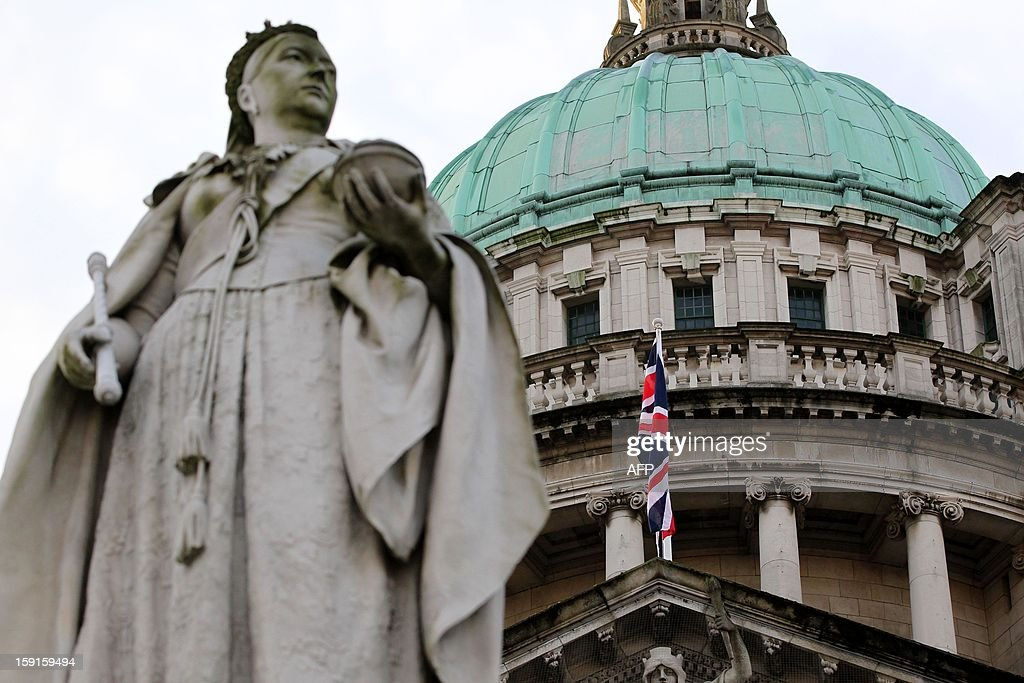 A staute of Queen Victoria stands in front of the union flag at Belfast City Hall in Belfast, Northern Ireland to mark the Duchess of Cambridge's 31st birthday on January 9, 2013. The British flag was hoisted over Belfast's City Hall for the first time since its removal a month ago sparked riots in Northern Ireland. On a sixth consecutive night of violence in the British province, protesters pelted police in the capital Belfast with petrol bombs, fireworks, bottles and stones. AFP PHOTO/ PETER MUHLY