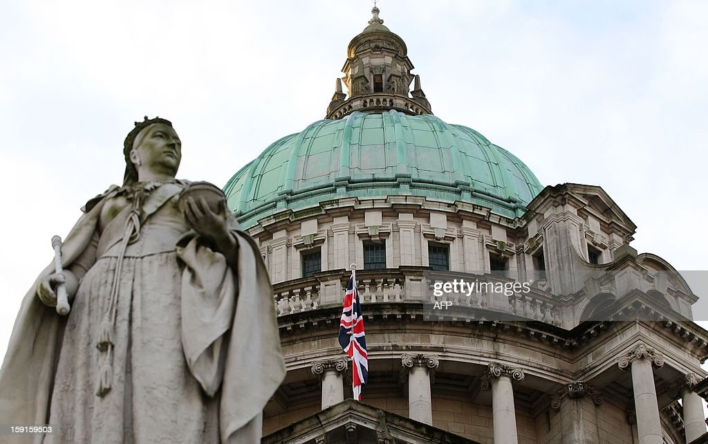 A staute of Queen Victoria stands in front of the union flag at Belfast City Hall in Belfast, Northern Ireland, hoisted to mark the Duchess of Cambridge's 31st birthday on January 9, 2013. The British flag was hoisted over Belfast's City Hall for the first time since its removal a month ago sparked riots in Northern Ireland. On a sixth consecutive night of violence in the British province, protesters pelted police in the capital Belfast with petrol bombs, fireworks, bottles and stones. AFP PHOTO/ PETER MUHLY