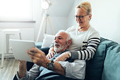 Elderly couple enjoying spending time together while using tablet at home.