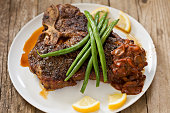 """""""A high angle close up of a plate with a T bone steak, mushroom sauce and green beans. Shot on a grungy old table."""""""