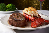 A juicy steak next to a succulent lobster in a white fancy restaurant. There is a plate of blurry broccoli in the background, and this delicious meal is paired with a red wine in a wine glass shown to
