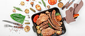 steak and sausage cooked on a grill with grilled vegetables in a cast iron pan on a white background, top view. Flat lay