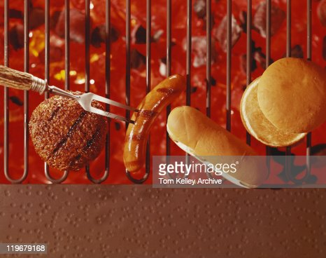 Steak, buns and sausage on barbecue grill, close-up