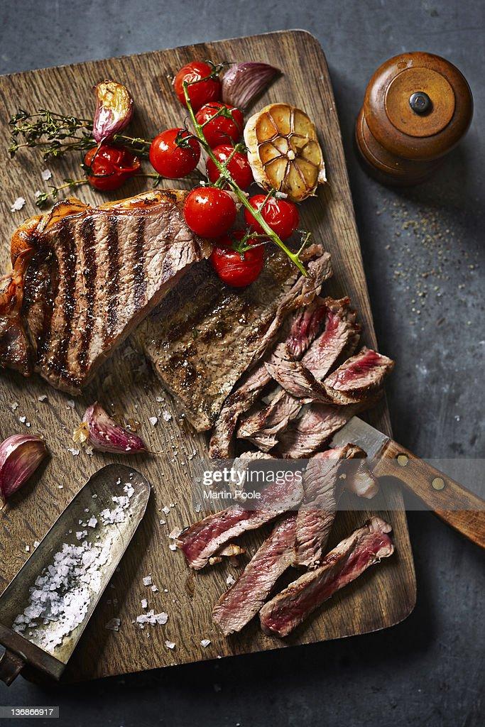 steak cut on board with roasted veg