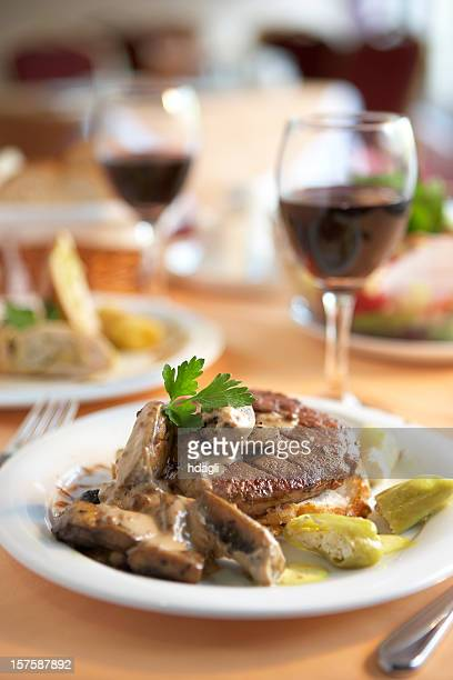 Steak dinner on a plate next to a glass of wine