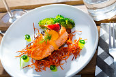 Dish of  tasty  steak of  fried salmon with smoked carrots, broccoli, cucumbers and fig on plate