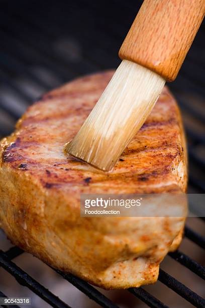 Steak on barbecue grill with basting brush, close up