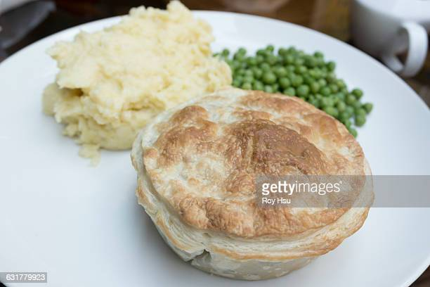 Steak pie with mashed potatoes and peas