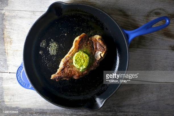 Steak with herb butter in a pan (seen from above)