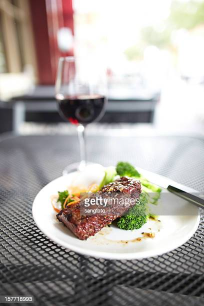 Steak with vegetable and red wine glass outdoors