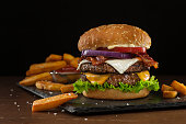 High resolution digital capture of a steakhouse-style double bacon cheeseburger with steak fries. This cheeseburger is made with two patties of ground steak, Cheddar and Monterey Jack cheeses, crispy