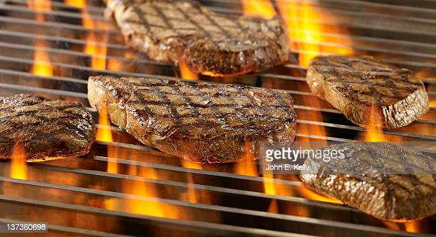 Steaks cooking on an open flame grill
