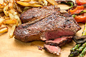 A high angle close up shot of a porterhouse steak, grilled vegetables and fries.